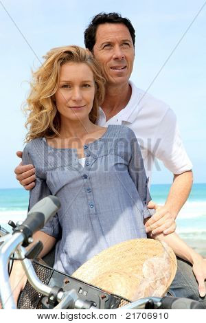 Couple with bike by the sea
