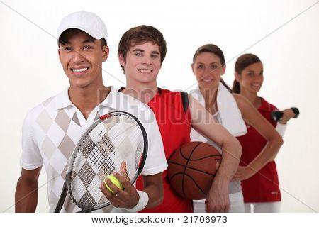 Cuatro adolescentes vestidos para diferentes deportes