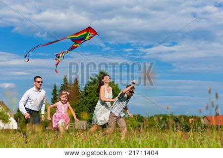 Happy family - mother, father, children - running over a green meadow in summer; they fly a kite