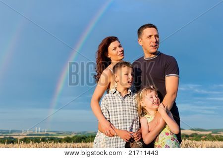 Happy family - mother, father, children - standing under a Rainbow in summer looking into a glorious future