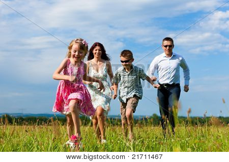 Happy family - mother, father, children - running over a green meadow in summer kicking a soccer ball