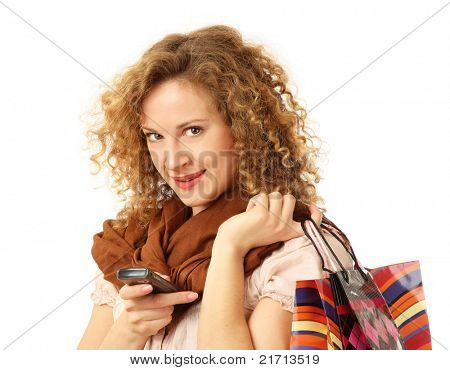 A beautiful woman with purchases and mobile phone on white