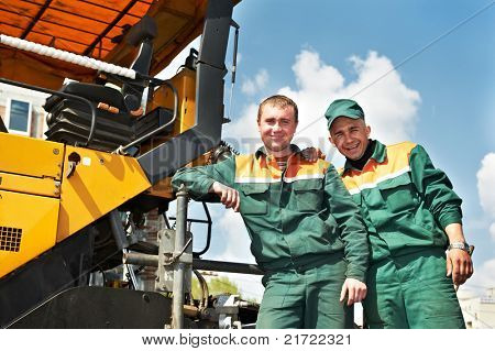 two happy road construction workers near asphalt paver machine