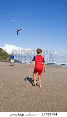 Little boy playing with kite and dad on the beach