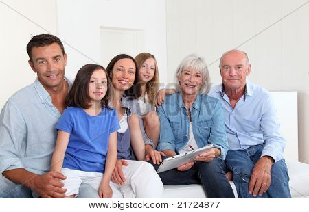 3-generation family sitting in couch with electronic tablet