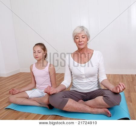 Senior woman with young girl doing yoga exercises
