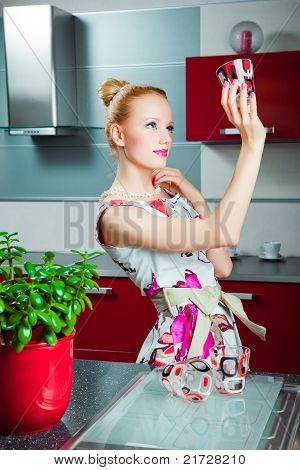 Housewife with clean glass in interior of kitchen