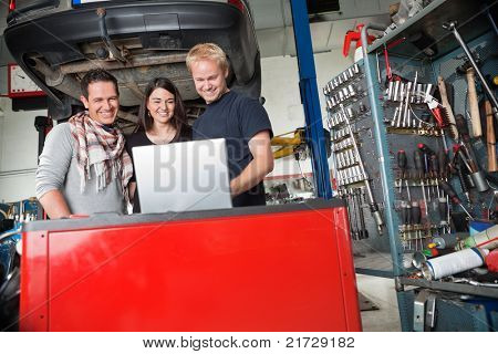 Young smiling couple standing with mechanic using laptop in auto repair shop