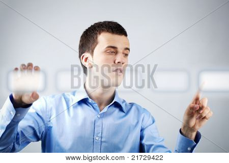 Image of businessman holding and pressing virtual button