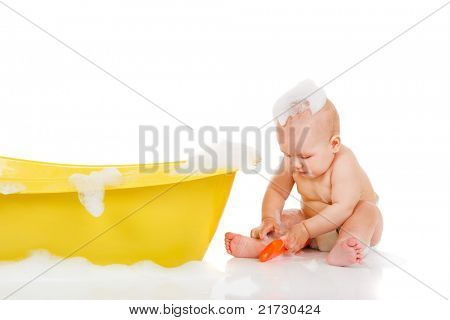 Cute baby with foam on head sits beside yellow bath