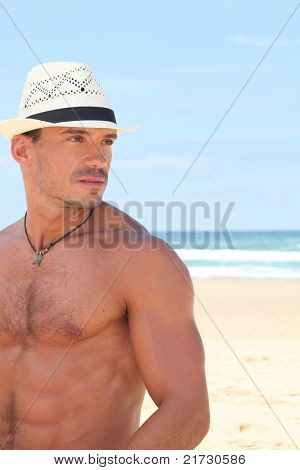 Dude posing in a straw hat on a sunny beach