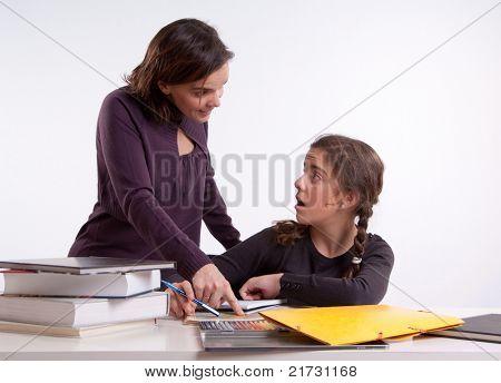 Teacher explaining her schoolwork to a young schoolgirl