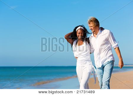 Happy couple - black woman and Caucasian man - walking and running down a beach in their vacation