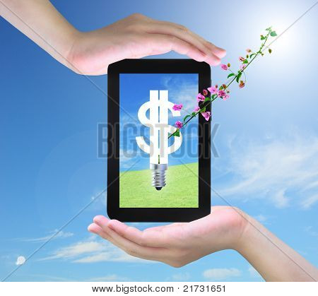 light bulb model of a dollar symbol and pink flower on tablet PC in women hand