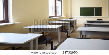 Empty beige classroom with wooden school desks and simple black chairs, view from desk on school board