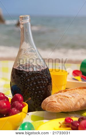 Picnic with wine bread and fruit at the beach