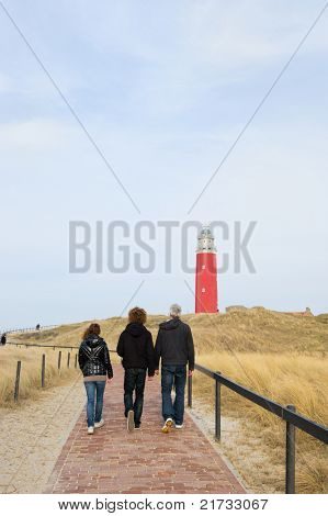 Three persons are walking to the red lighthouse