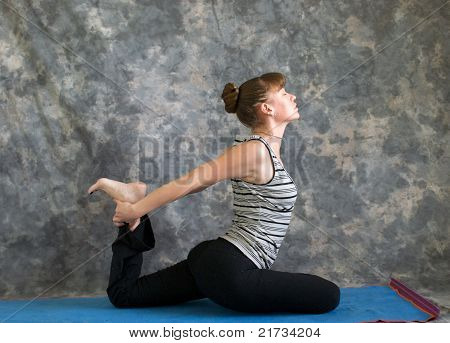 Young Woman Doing Yoga Posture Kapotasana Or Pigeon Pose Variation 1