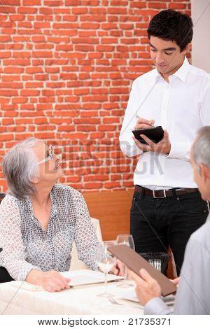 Garçom jovem tendo um pedido em um restaurante