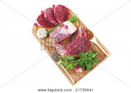 butchery : fresh raw beef lamb big rib and fillet ready to cooking with green stuff on wooden plate isolated over white background