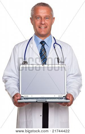 Photo of a mature adult male doctor, smiling to camera and holding a laptop computer with clipping path for the blank screen to add your own image of message, isolated on a white background.
