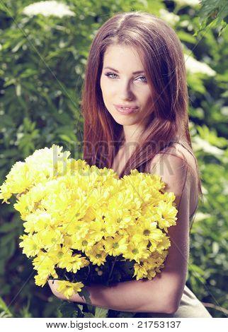 Woman holding yellow flowers . otdoor shoot