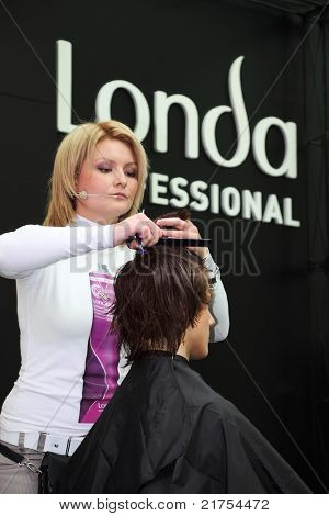 "MOSCOW - OCTOBER 2: Hairdresser makes hairstyle at master class from Londa at XVII International Festival ""World of Beauty - 2010"" in exhibition complex Gostiny Dvor on October 2, 2010, Moscow, Russia"
