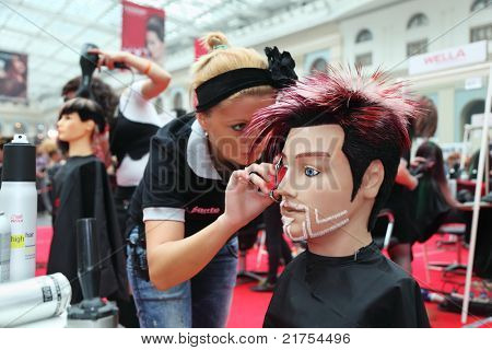 "MOSCOW - OCTOBER 2: Hairdresser makes hairstyle for manikin at XVII International Festival ""World of Beauty - 2010"" in exhibition complex Gostiny Dvor, on October 2, 2010 in Moscow, Russia."