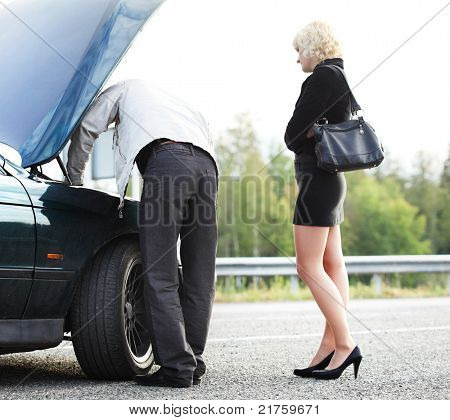 Young blonde woman standing by broken car and waiting her boyfriend
