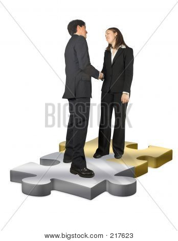 Business Couple Shaking Hands On Puzzle Pieces