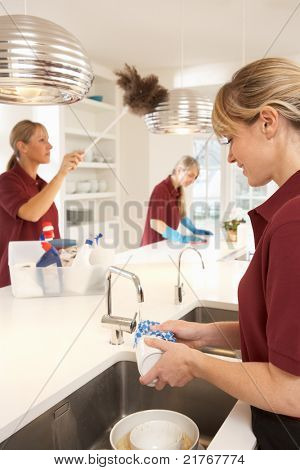 Team Of Commercial Cleaners Working In Domestic Kitchen