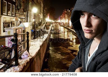 Young cool street style fashion male model posing in Amsterdam at night