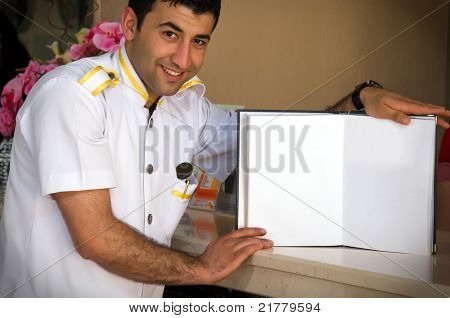 Bellboy holding a blank notebook for your text vignetted.