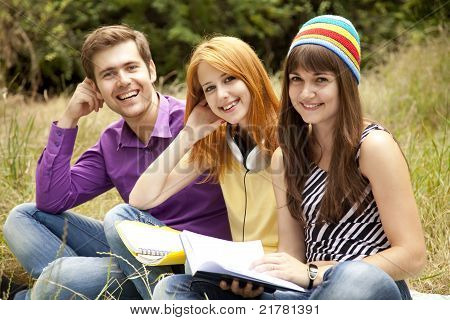 Three students at outdoor doing homework