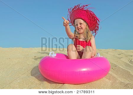happy kid on vacations on beach pointing at bland copy space