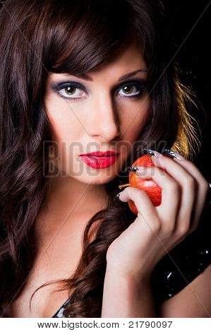 Beautiful brunette girl with apple on black