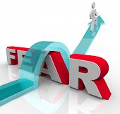 stock photo of overcoming obstacles  - A man jumps over the word fear on an arrow - JPG