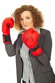 foto of semi-formal  - Upset executive woman standing in semi profile and wearing boxing gloves isolated on white background - JPG