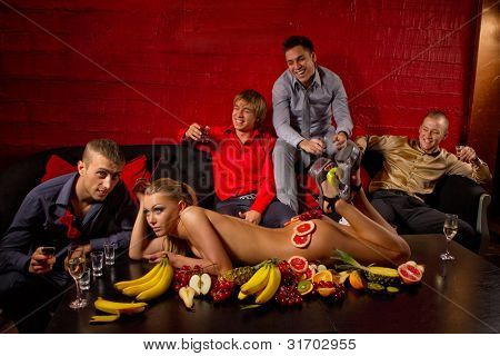 Four guys having fun with woman decorated  by fruits