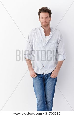 Handsome young man standing over white background, wearing shirt and jeans.