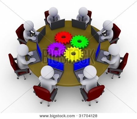 Businessmen Around Table With Laptops And Four Cogs