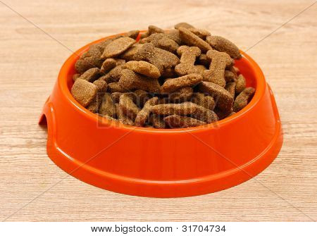 dry dog food in orange bowl on wooden background