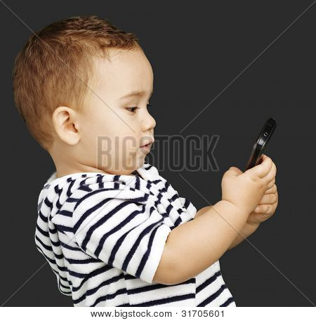 portrait of funny kid touching mobile over black background