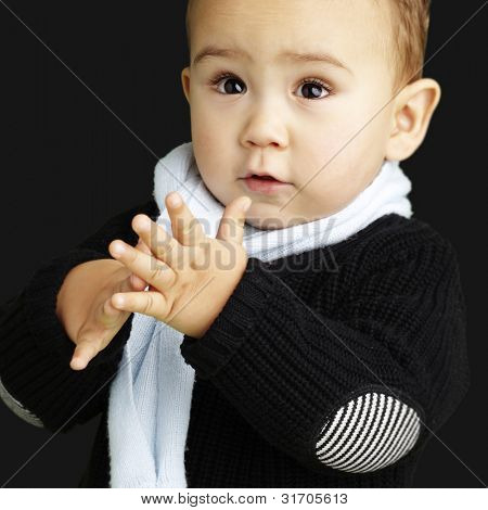 portrait of adorable kid clapping against a black background