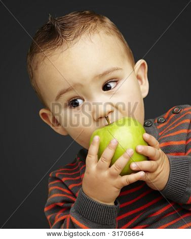 portrait of a handsome kid biting a green apple over black back
