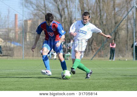 KAPOSVAR, HUNGARY - MARCH 17: Mark Barcsay (in blue) in action at the Hungarian National Championship under 18 game between Kaposvar(white)  and Videoton (blue) March 17, 2012 in Kaposvar, Hungary.