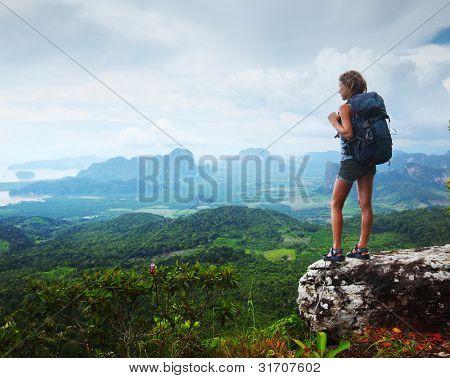 Joven turista con mochila goza de vistas al valle desde la cima de una montaña