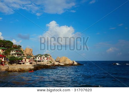 Rocky coast with buildings and blue sea with cloudy sky