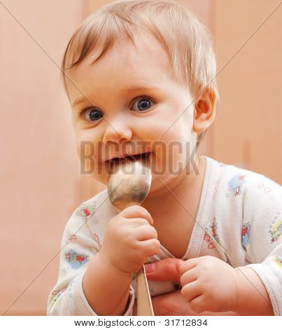 Portrait of happy baby girl holding spoon in mouth