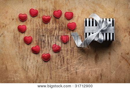Caja de regalo de vacaciones había atado arco grande de plata con pequeños corazones en forma de corazón. En la vieja madera backgrou